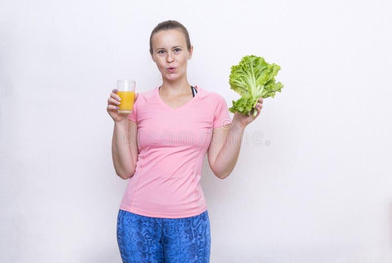 1 λευκιά νέα γυναίκα σε μια ρόδινη αθλητική κορυφή σε μια χαρούμενη έκφραση που κρατά ένα ποτήρι του χυμού και μια δέσμη της πράσ στοκ εικόνες με δικαίωμα ελεύθερης χρήσης