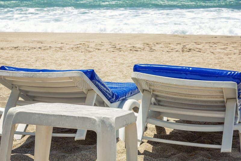 Λευκοί αργόσχολοι με τα μπλε στρώματα σε μια δημόσια αμμώδη παραλία θαλασσίως E r στοκ εικόνες με δικαίωμα ελεύθερης χρήσης