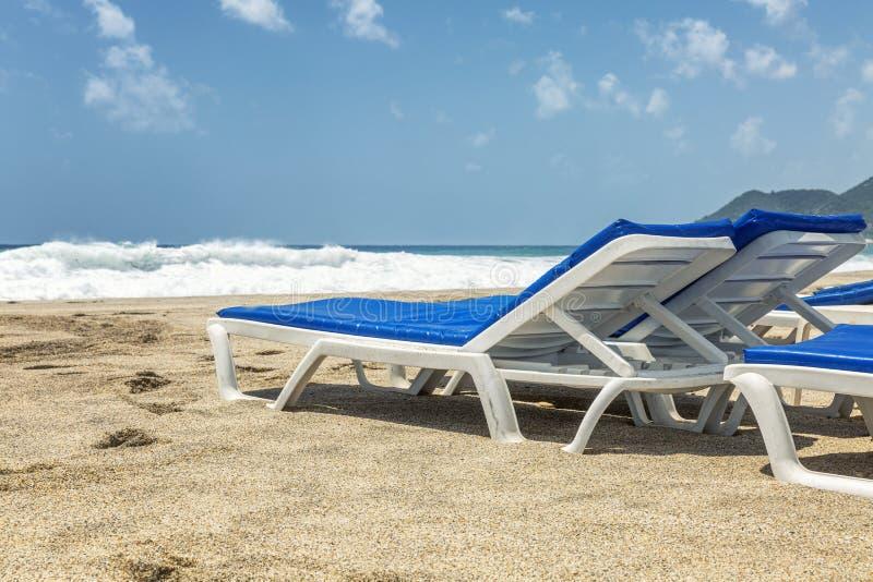 Λευκοί αργόσχολοι με τα μπλε στρώματα σε μια δημόσια αμμώδη παραλία θαλασσίως E r στοκ φωτογραφία με δικαίωμα ελεύθερης χρήσης