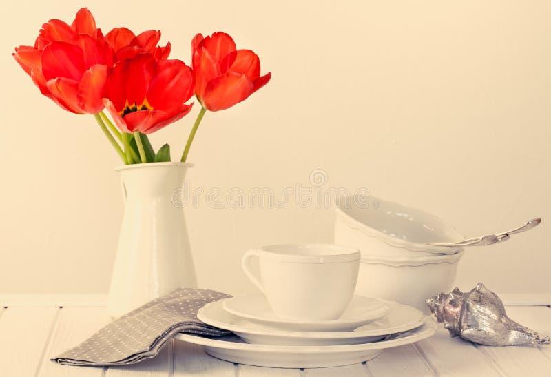 Λευκοί πιάτα, κύπελλα, μαχαιροποιός και τουλίπες στοκ φωτογραφία