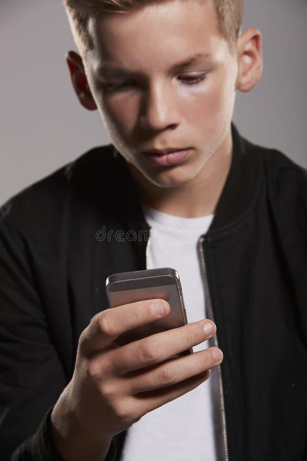 Λευκός έφηβος που καταναλώνει το κινητό τηλέφωνο, μέση, κάθετη στοκ φωτογραφίες με δικαίωμα ελεύθερης χρήσης