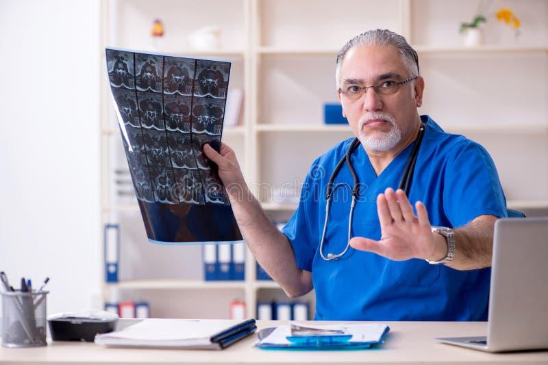 Λευκός γενειοφόρος παλαιός ακτινολόγος γιατρών που εργάζεται στην κλινική στοκ εικόνα