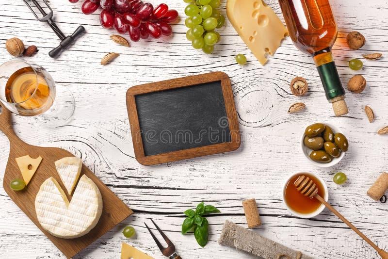 Λευκός πίνακας μπουκαλιών, σταφυλιών, μελιού, τυριών, wineglass και κιμωλίας κρασιού στο λευκό ξύλινο πίνακα στοκ φωτογραφία με δικαίωμα ελεύθερης χρήσης