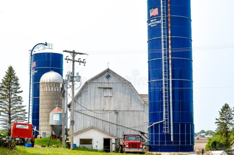 Λευκό αχυρώνα, μπλε σιλό και κόκκινα φορτηγά παραλαβής στοκ εικόνα με δικαίωμα ελεύθερης χρήσης
