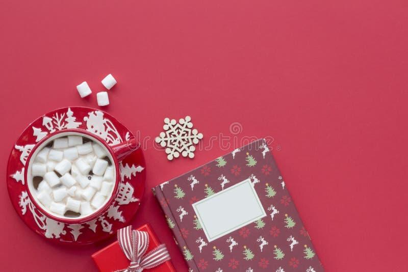 Λευκό ζαχαρωτό κακάο σε κόκκινη χριστουγεννιάτικη κούπα και βιβλίο σε κόκκινο φόντο στοκ εικόνες