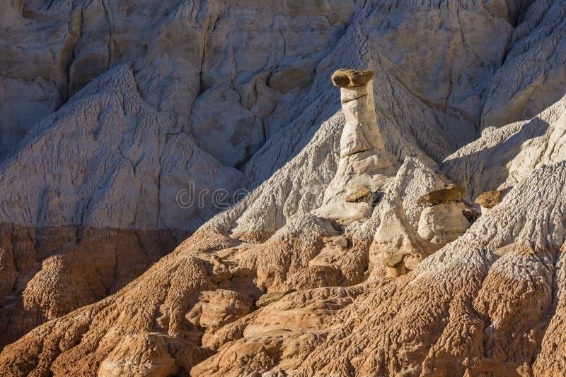 Λευκό και σοκολάτα Hoodoos ενάντια στους μπλε απότομους βράχους στοκ φωτογραφίες