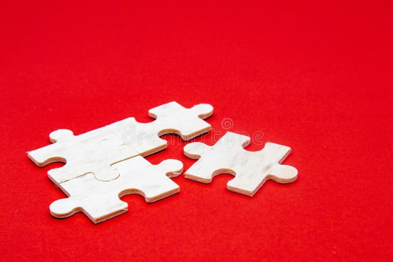 Λευκό ξύλινο παζλ σε κόκκινο φόντο για εξάσκηση διαλογισμού, δεξιότητες επίλυσης προβλημάτων και υπομονή επιχείρηση στοκ εικόνες