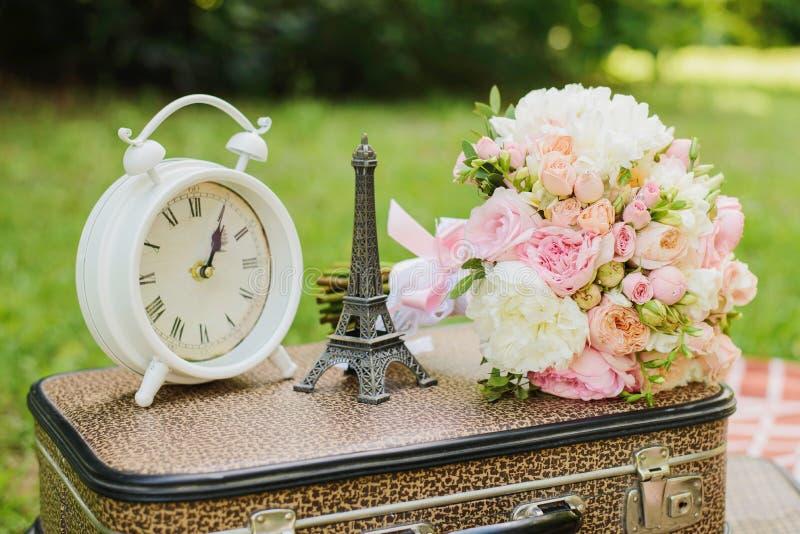 Λευκό ρολόι, ένα αγαλματίδιο του πύργου του Άιφελ, το μπουκέτο της νύφης είναι στη βαλίτσα στοκ εικόνες