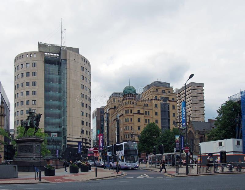 Λεωφορεία και πέρασμα πεζών ο δρόμος στην πόλη τετραγωνικό Λιντς με τα ψηλά κτίρια γραφείων της σειράς πάρκων στοκ φωτογραφία με δικαίωμα ελεύθερης χρήσης