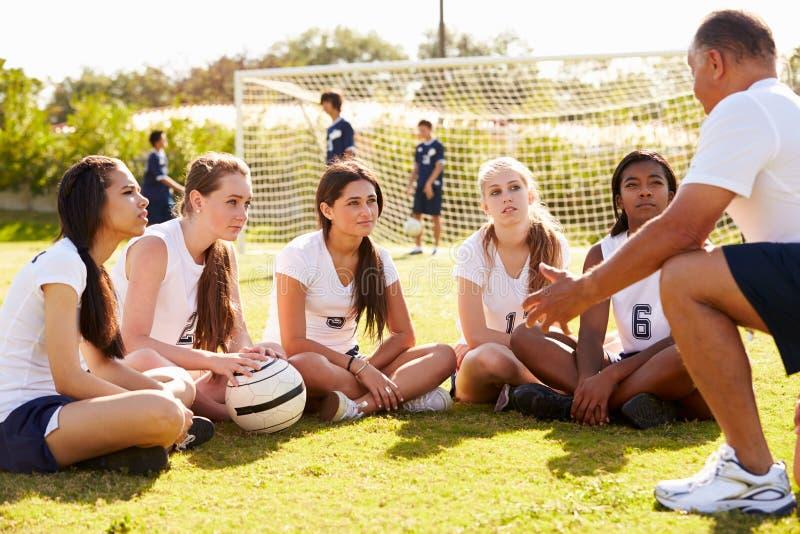Λεωφορείο που δίνει τη συζήτηση ομάδας στη θηλυκή ομάδα ποδοσφαίρου γυμνασίου στοκ φωτογραφία με δικαίωμα ελεύθερης χρήσης