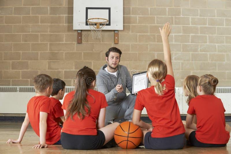 Λεωφορείο που δίνει τη συζήτηση ομάδας στο ομάδα μπάσκετ δημοτικού σχολείου στοκ φωτογραφίες