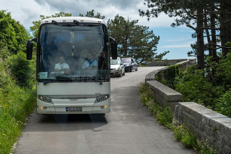 Λεωφορείο που προσπαθεί να κάνει το χώρο στο στενό ελικοειδή δρόμο Kotor στοκ εικόνες