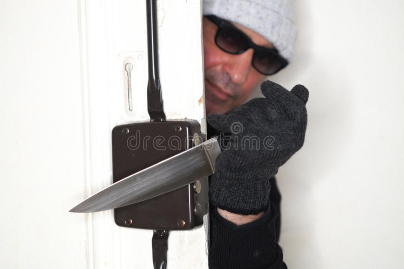 Ληστής που τιτιβίζει από μια πόρτα στοκ εικόνα