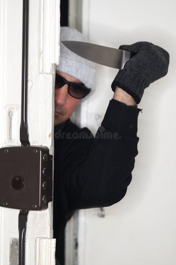Ληστής που τιτιβίζει από μια πόρτα στοκ φωτογραφίες