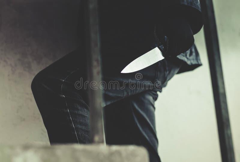 Ληστής που φορά μια μάσκα που περπατά στα σκαλοπάτια με ένα μαχαίρι για το λάφυρο στοκ φωτογραφία