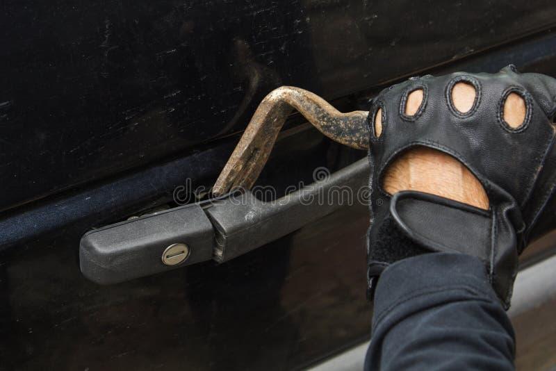 Ληστής στα μαύρα γάντια που σπάζουν στην κλειδαριά αυτοκινήτων με το εργαλείο λοστών στοκ φωτογραφία με δικαίωμα ελεύθερης χρήσης