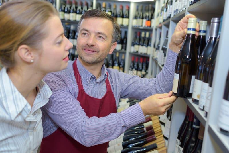 Λιανοπωλητής κρασιού που συμβουλεύει τον πελάτη στοκ εικόνες