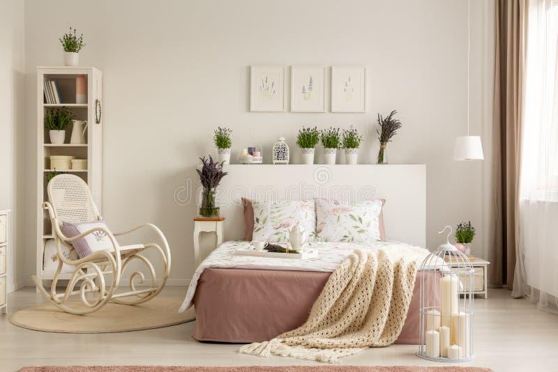 Λικνίζοντας καρέκλα δίπλα στο κρεβάτι με το κάλυμμα στο provencal εσωτερικό κρεβατοκάμαρων με τις εγκαταστάσεις και τις αφίσες Πρ στοκ φωτογραφία με δικαίωμα ελεύθερης χρήσης