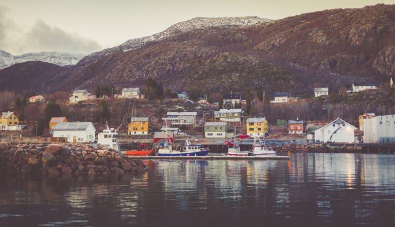 Λιμάνι με τις δεμένες βάρκες και γιοτ με τις χιονοσκεπείς αιχμές στο υπόβαθρο στο ψαροχώρι στοκ εικόνες