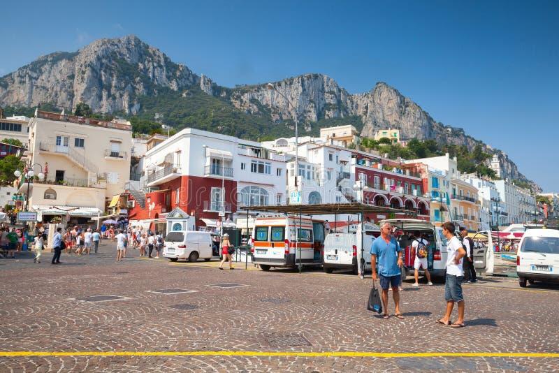 Λιμένας Capri με τους τουρίστες, αυτοκίνητα, προσόψεις οικοδόμησης στοκ εικόνα
