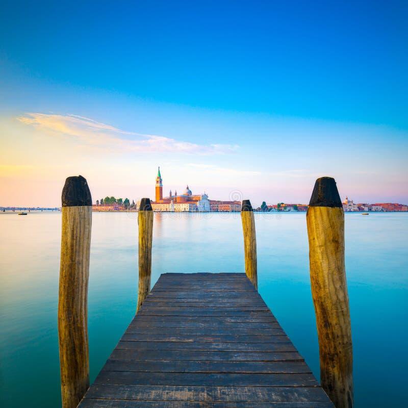 Λιμνοθάλασσα της Βενετίας, ξύλινος αποβάθρα ή λιμενοβραχίονας και πόλοι και εκκλησία στην ΤΣΕ στοκ φωτογραφία με δικαίωμα ελεύθερης χρήσης