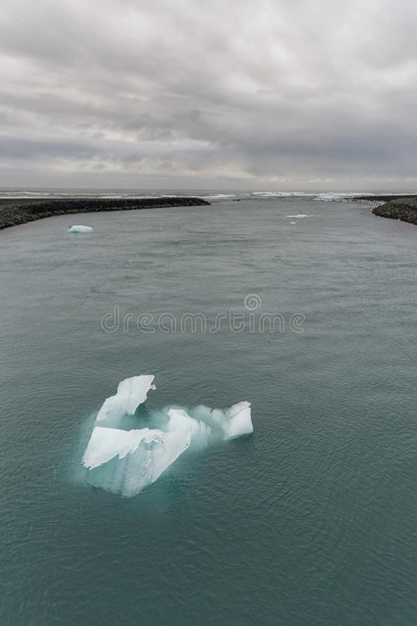 Λιμνοθάλασσα παγετώνων Jokulsarlon στην Ισλανδία Νεφελώδεις ουρανός, ωκεανός και παγόβουνο στοκ εικόνα