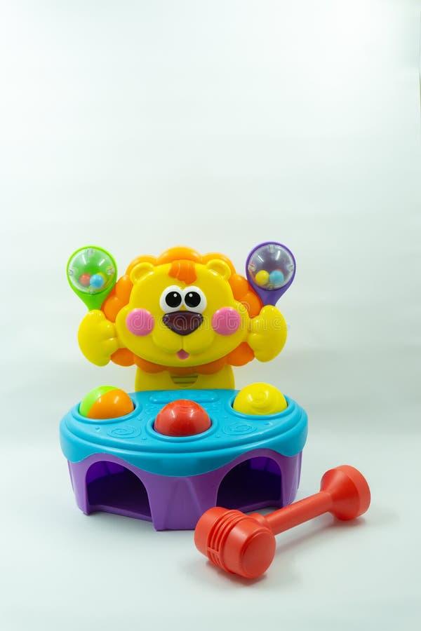Λιοντάρι, σφαίρα και σφυρί παιχνιδιών μωρών φιαγμένα από πλαστικό στο άσπρο υπόβαθρο Χαριτωμένο πορτοκαλί λιοντάρι παιχνιδιών παι στοκ εικόνες