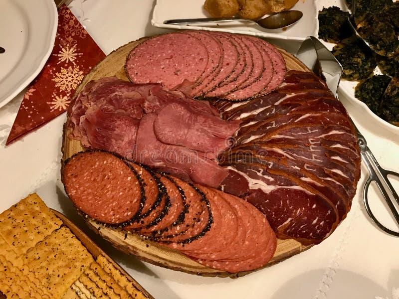 Λιχουδιές Antipasto - τεμαχισμένες κρέας, ζαμπόν, σαλάμι, pastrami/pastirma και φέτες γλωσσών βόειου κρέατος στον ξύλινο πίνακα στοκ φωτογραφία