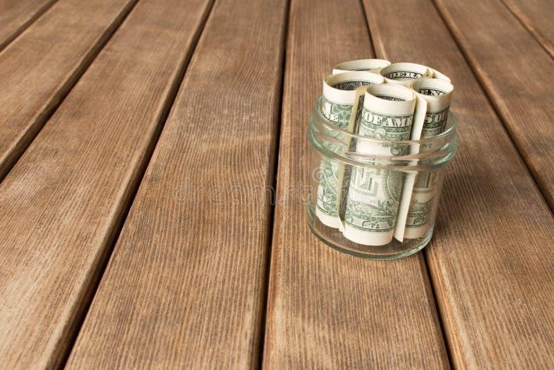 Λογαριασμοί δολαρίων σε ένα βάζο γυαλιού σε έναν ξύλινο πίνακα η έννοια του Π στοκ φωτογραφίες