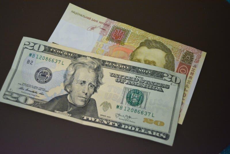 Λογαριασμοί εγγράφου στο μέγεθος του Δολ ΗΠΑ 20 $ είκοσι αμερικανικά δολάρια και UAH 100 ουκρανικό hryvnia εκατό σε ένα καφετί υπ στοκ εικόνα με δικαίωμα ελεύθερης χρήσης
