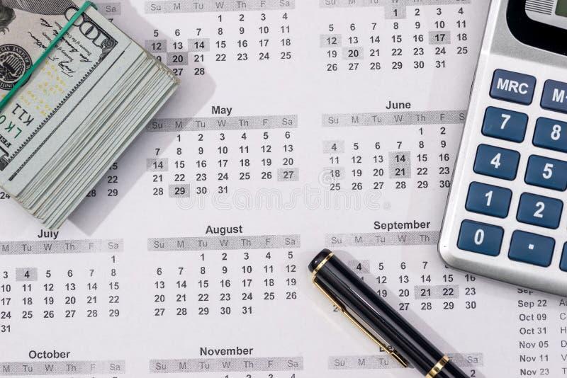 Λογαριασμοί εκατό δολαρίων με το ημερολόγιο, υπολογιστής στοκ φωτογραφία