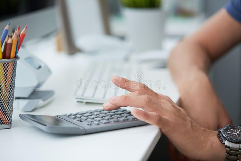 Λογιστής επιχειρηματιών που χρησιμοποιεί τον υπολογιστή και τον υπολογιστή γραφείου για τον υπολογισμό της χρηματοδότησης στην κι στοκ φωτογραφίες
