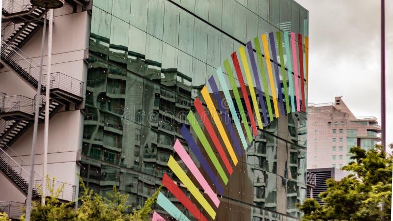 Λογότυπο επιχείρησης αριθ. σε ένα εξωτερικό κτήριο γυαλιού με κάποια πρασινάδα στοκ φωτογραφίες με δικαίωμα ελεύθερης χρήσης