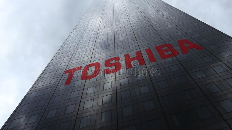 Λογότυπο εταιριών Toshiba σε μια πρόσοψη ουρανοξυστών που απεικονίζει τα σύννεφα Εκδοτική τρισδιάστατη απόδοση στοκ φωτογραφία με δικαίωμα ελεύθερης χρήσης