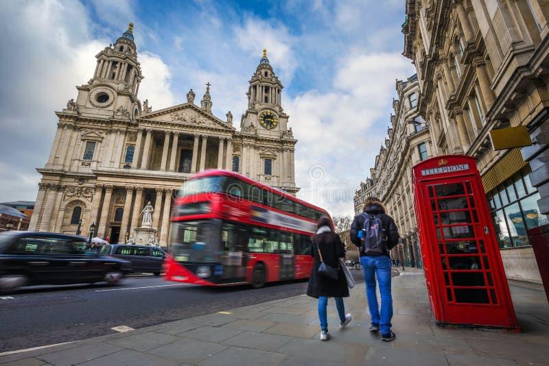 Λονδίνο, Αγγλία - ζεύγος τουριστών που περπατά από ένα παραδοσιακό κόκκινο τηλεφωνικό κιβώτιο με το κόκκινο διώροφο λεωφορείο στοκ εικόνες με δικαίωμα ελεύθερης χρήσης