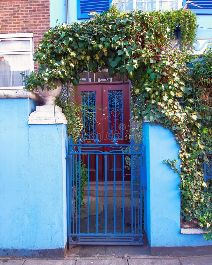 Λονδίνο, λόφος Notting, ζωηρόχρωμη μπλε είσοδος με το φύλλωμα και ξύλινη πόρτα στοκ φωτογραφία με δικαίωμα ελεύθερης χρήσης