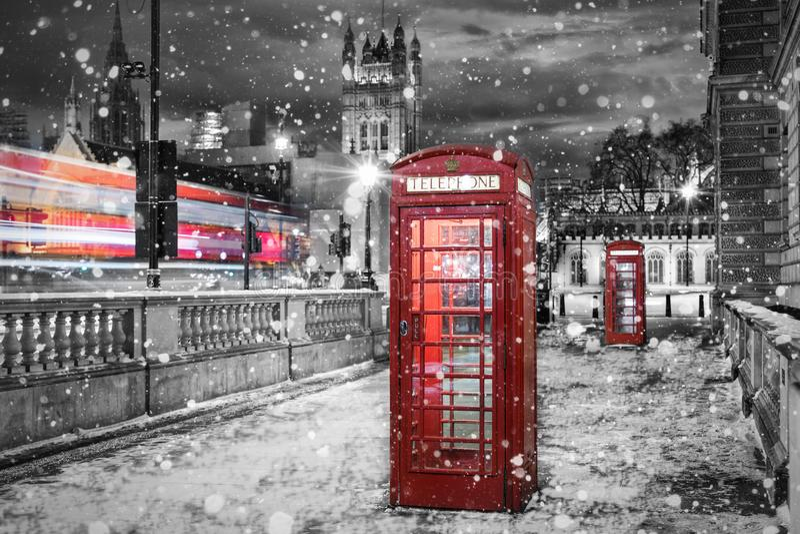 Λονδίνο στο χειμώνα: κόκκινα τηλεφωνικά κύτταρα με το μειωμένο χιόνι στοκ εικόνα