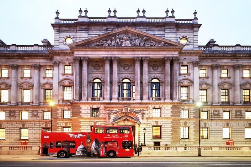ΛΟΝΔΙΝΟ, UK - 26 ΝΟΕΜΒΡΊΟΥ 2018: Κόκκινο διπλό λεωφορείο καταστρωμάτων γύρου πόλεων του Λονδίνου μπροστά από το όμορφο κτήριο με  στοκ φωτογραφία