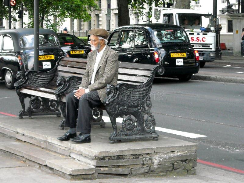 Λονδίνο μια παλαιότερη συνεδρίαση σε έναν πάγκο στην κυκλοφορία στοκ εικόνες
