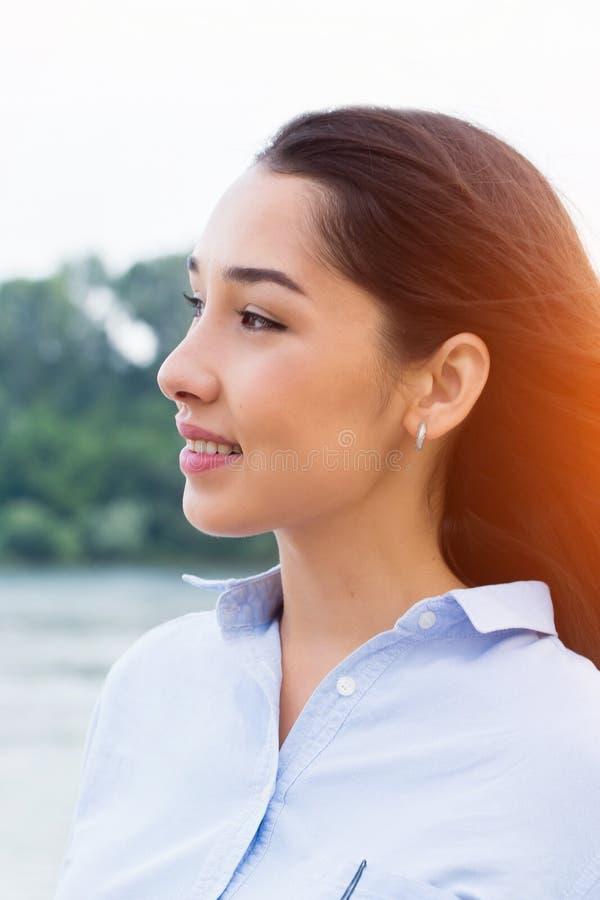 Λοξά πορτρέτο κινηματογραφήσεων σε πρώτο πλάνο της χαμογελώντας γυναίκας brunette με τη φυσική ομορφιά και κανενός makeup στο ηλι στοκ φωτογραφία με δικαίωμα ελεύθερης χρήσης