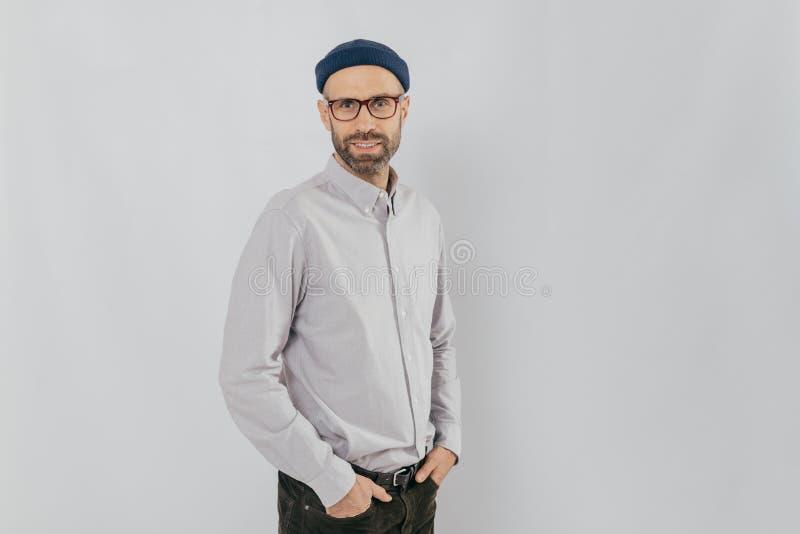 Λοξά πυροβοληθείς του όμορφου ευτυχούς ατόμου φορά το μοντέρνο καπέλο, κρατά παραδίδει τις τσέπες, στέκεται στο άσπρο κλίμα με το στοκ εικόνα με δικαίωμα ελεύθερης χρήσης