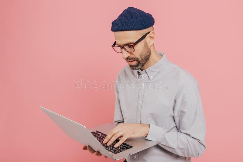 Λοξά πυροβοληθείσες του ελκυστικού ατόμου οι στάσεις μπροστά από τον ανοιγμένο φορητό προσωπικό υπολογιστή, λειτουργούν σε Διαδίκ στοκ εικόνα
