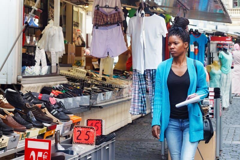 ΛΟΥΒΑΙΝ, ΒΕΛΓΙΟ - 5 ΣΕΠΤΕΜΒΡΊΟΥ 2014: Άγνωστη ελκυστική νέα αφρικανική Ευρωπαία γυναίκα που περπατά στο Grote Markt στοκ εικόνες