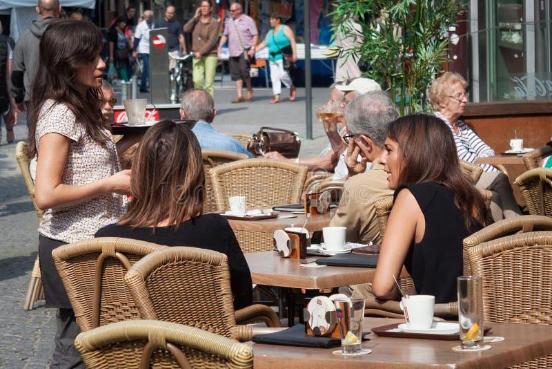 ΛΟΥΒΑΙΝ, ΒΕΛΓΙΟ - 5 ΣΕΠΤΕΜΒΡΊΟΥ 2014: Οι άγνωστοι άνθρωποι στηρίζονται στον υπαίθριο καφέ στο Λ Vanderkelen ST στο Λουβαίν στοκ εικόνες