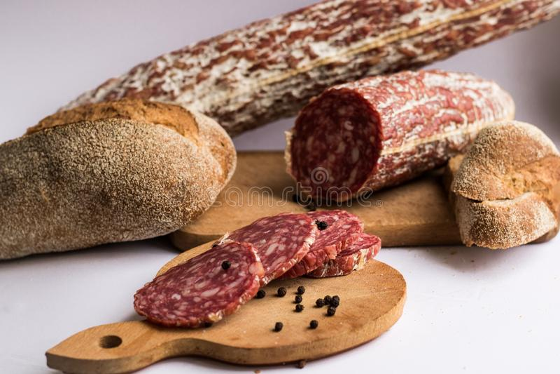 Λουκάνικα και σκοτεινό ψωμί που απομονώνονται στο άσπρο υπόβαθρο στοκ φωτογραφίες