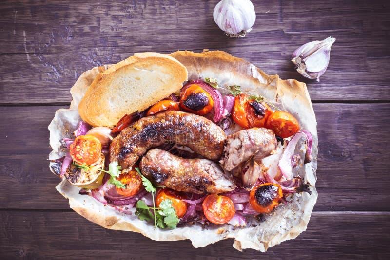 Λουκάνικα με το κρεμμύδι και ντομάτες στην παλαιά ξύλινη επιφάνεια στοκ φωτογραφίες με δικαίωμα ελεύθερης χρήσης