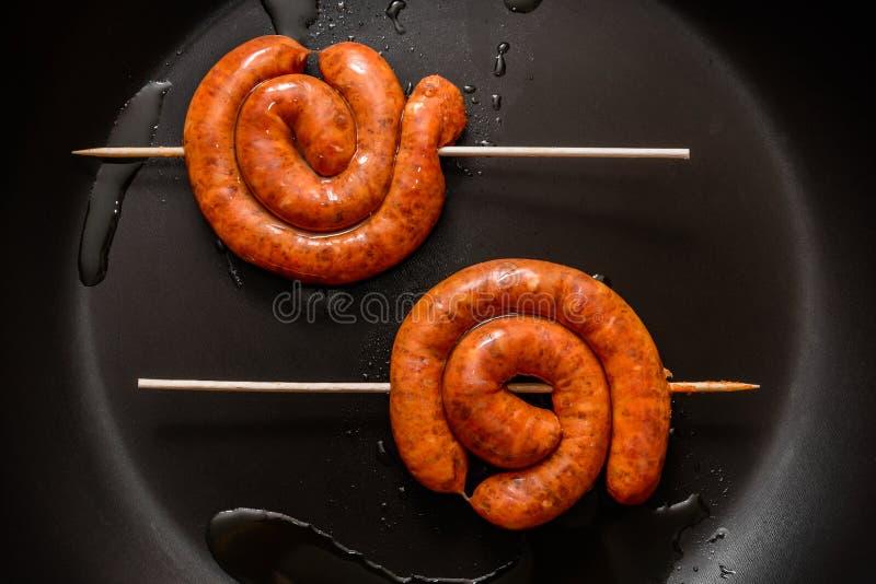 Λουκάνικα χοιρινού κρέατος σε ένα τηγάνι στοκ εικόνα