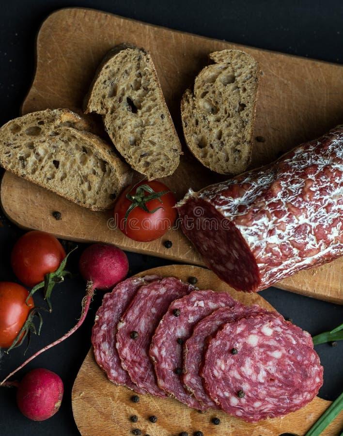 Λουκάνικο, ψωμί και υπόβαθρο κομματιών λαχανικών στοκ φωτογραφίες