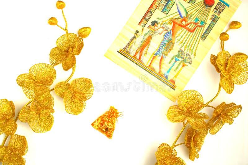 Λουλούδια και εγκαταστάσεις του χρυσού χρώματος, ενός σχεδίου στον πάπυρο και των διακοσμήσεων σε μια σακούλα στοκ φωτογραφίες