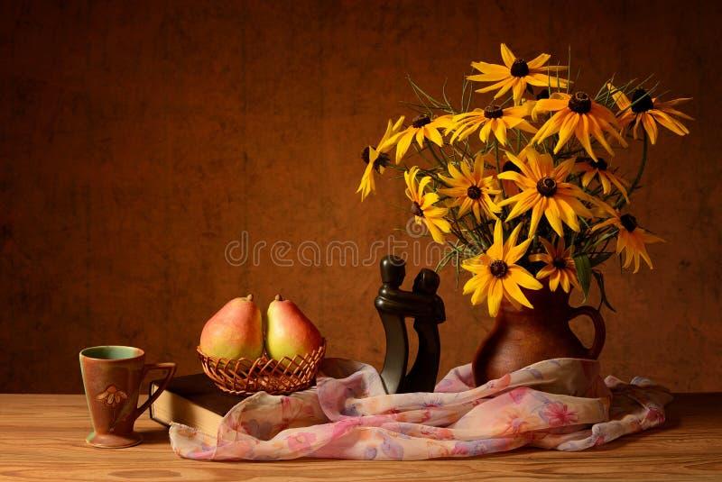 Λουλούδια σε ένα βάζο, τα βιβλία και τα αχλάδια στοκ εικόνες